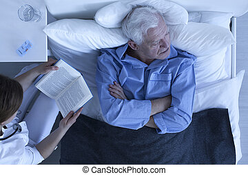 Tired by hospital life - Nurse reading a book to the senior...