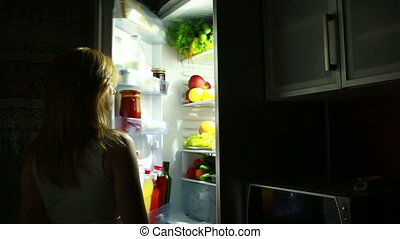 Woman night takes an apple from the fridge. hungry woman