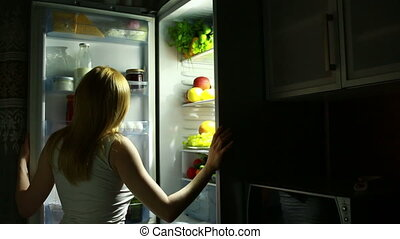 Girl looks in the fridge at night. night meal. Woman wants...