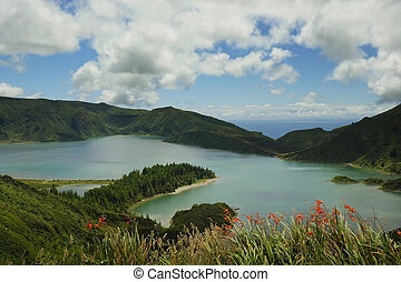 amazing landscape view of crater volcano lake in Sao Miguel island of Azores Portugal with flowers beautiful turquoise water