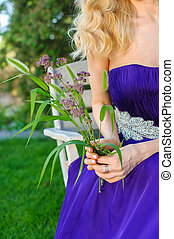 Woman holding bouquet of wildflowers. Blonde Beautiful woman...