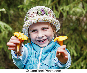 Young girl with chanterelle mushrooms. - Portrait of smiling...