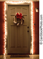 Christmas lights and wreath on front door at night - White...