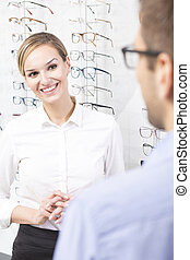 Smiling optician saleswoman with client in optician store