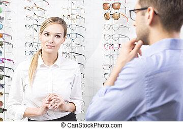 At eyewear store - Young man and female seller at eyewear...