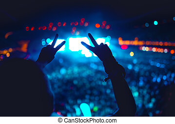 Silhouette of hands showing love for artists at concert,...