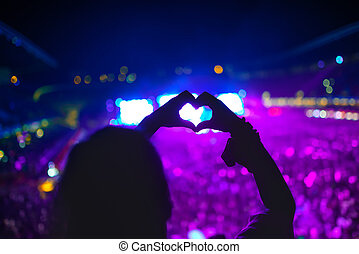 heart shaped hands at concert, woman at festival loving the...