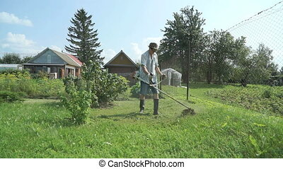Gardener cuts the grass with a lawnmower outdoors