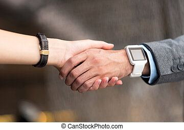 Pleasant colleagues shaking hands