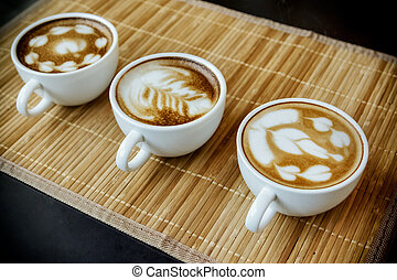 Three cups of cafe' latte with three shapes of latte art