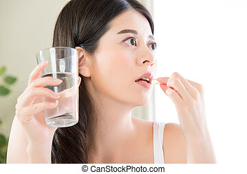 young beautiful asian woman eating nutritional supplement...