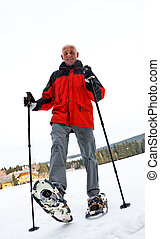 Senior at the snow-shoe walking in winter - Older man in...