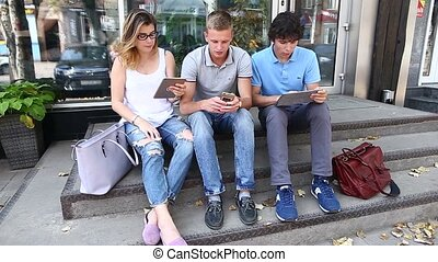 Young three friends sitting floor in the street, talking, using