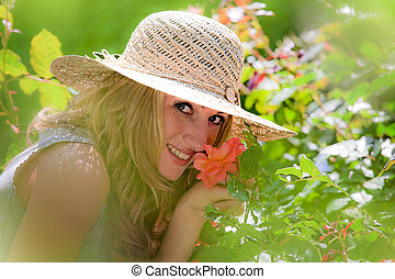 Woman smelling a rose in a garden