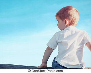 Little child boy sitting pensive looking away outdoors over...