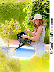 Woman pours flowers in the garden with watering can