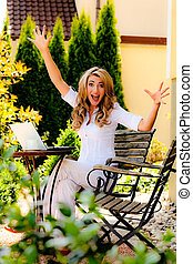 Successful, smiling woman with laptop in garden