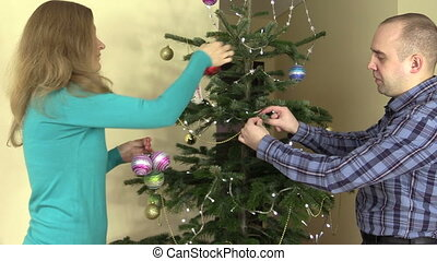 man husband and woman wife decor Christmas tree with ball...