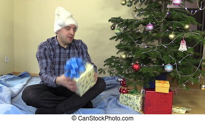 Funny family man catch gift box and put under Christmas tree...
