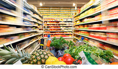 Shopping cart with fruit vegetable food in supermarket -...