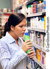 Women in Drogerimarkt buys shampoo - Young woman in a drug...