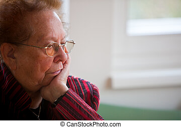 Thoughtful senior citizen - An old woman sits pensively at...