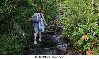 Hiker woman with backpack walking on a forest trail in the mountains on the background a waterfall. Hiking. Adventure in the forest.