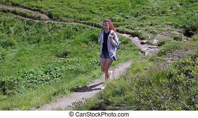Woman traveler is walking through the mountains and forests...