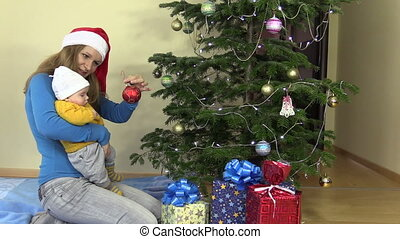 young mother with infant baby in hands hang Christmas tree toy