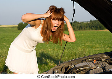 woman bent over car engine - young woman bent over car...