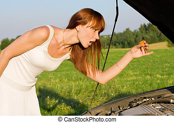 young woman bent over car engine - young woman with oil...