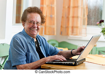 Active senior citizen with a laptop in Arts - Old woman with...