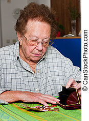 Senior citizen counts their money from pension - Old woman...