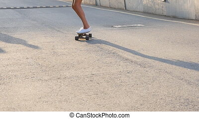 Woman skateboarding at sunrise. Legs on the skateboard,...