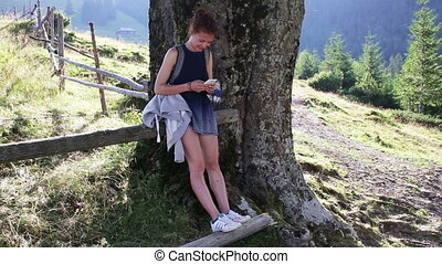 Young beautiful woman using mobile phone under a tree in the mountains