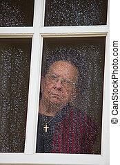 pensive looks sad senior citizen out of a window