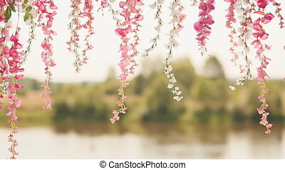 Artificial flowers against the backdrop of the river. Delicate flowers hang down.