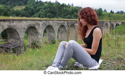 Girl dancing while sitting near the old viaduct in the...