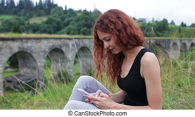 The girl writes sms sitting near the old viaduct in the mountains