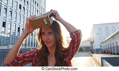Girl with a device of virtual reality in the city summer