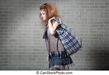 Tired redhaired woman with shopping bag. brick wall as...