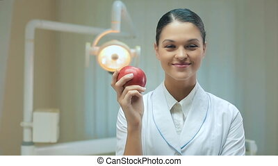 Woman dentist with apple - Smiling Woman dentist with apple...