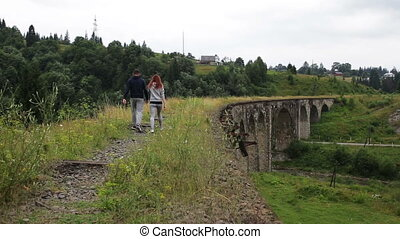 A couple walks along the old viaduct in the mountains.