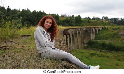 Girl sitting on the old viaduct.