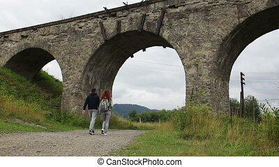 Happy couple walking along the road under the old viaduct.