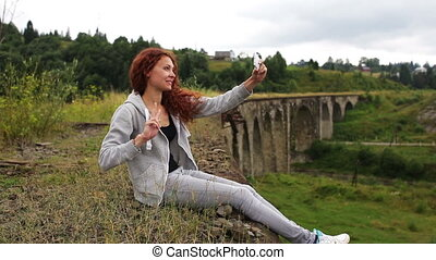 Girl doing selfie sitting on the old viaduct.