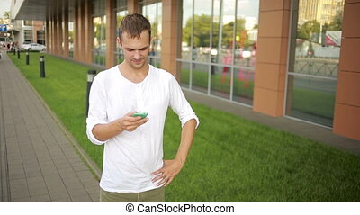 sweaty man is standing on the street and writing in phone. voice call