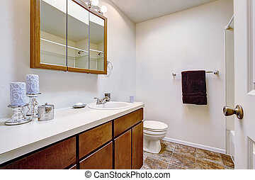 White bathroom with brown cabinets in old American house