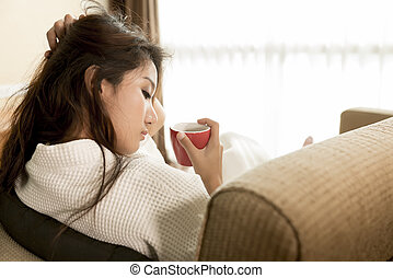 Young Asian woman relaxing with red mug coffee, tea on her...