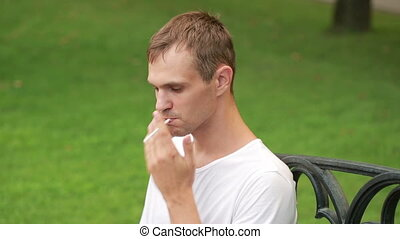 Man smoking thin cigarette at the park - Man smoking...